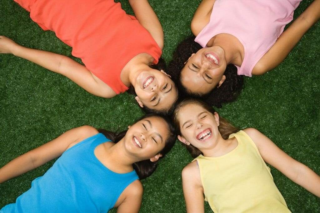 Four kids laying on artificial turf